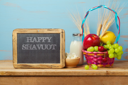 jewish home: Happy Shavuot greeting design with milk and fruits basket on wooden table.