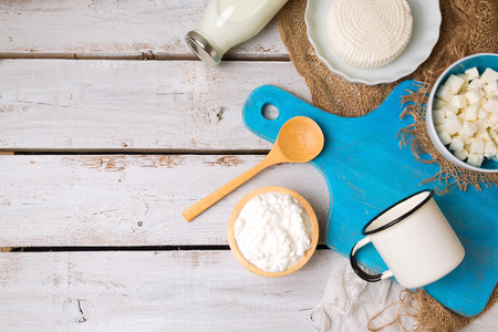 diet food: Milk and cottage cheese with cutting board on rustic background. View from above. Flat lay