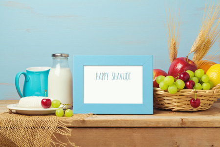 jewish home: Poster mock up template for Jewish holiday Shavuot. Milk and fruits on wooden table. Stock Photo