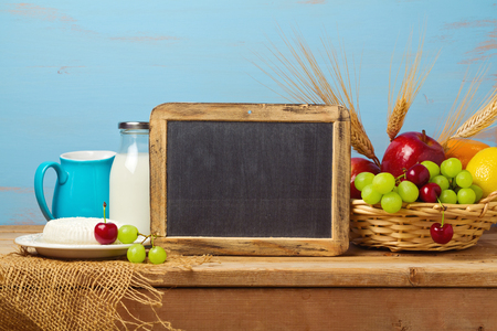 jewish home: Chalkboard  with fruit basket and milk on wooden table. Jewish holiday Shavuot background with place for text