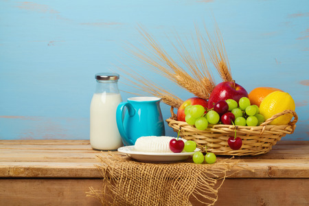 shavuot: Fruit basket and dairy products on wooden table. Jewish holiday Shavuot background