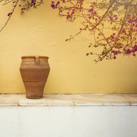 mediterranian houses: Greek village house detail. Vintage vase over wall background