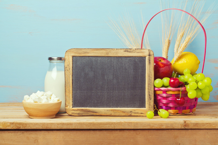 jewish home: Jewish holiday Shavuot background with chalkboard, milk and fruit basket