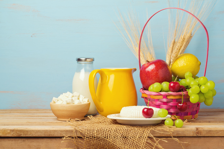 jewish home: Fruits, milk and cheese on wooden table. Jewish holiday Shavuot background
