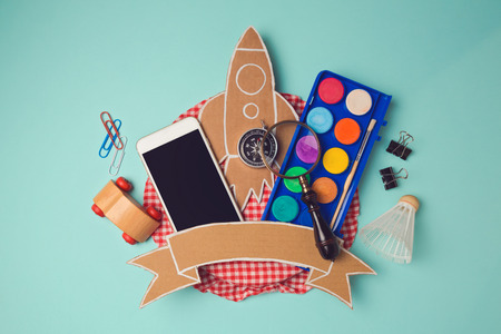 header image: Back to school badge design with smartphone and cardboard rocket. Creative design hero header image. View from above. Flat lay