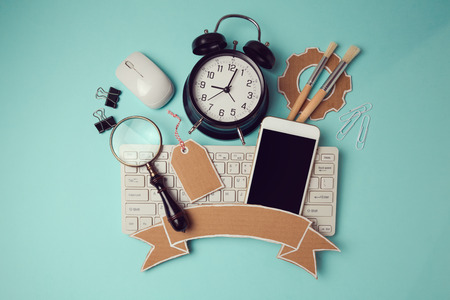 header image: Back to school badge design with smartphone, keyboard and clock. Creative design hero header image. View from above. Flat lay