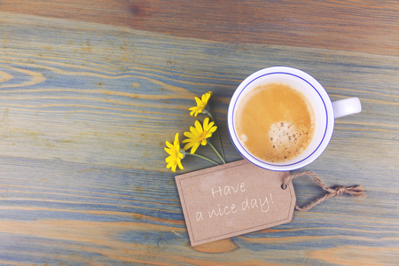 Coffee cup and daisy flowers with wish cardboard label on wooden table. Have a nice day romantic message. View from above