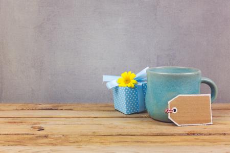 木桌上放着咖啡杯和鲜花礼品盒。