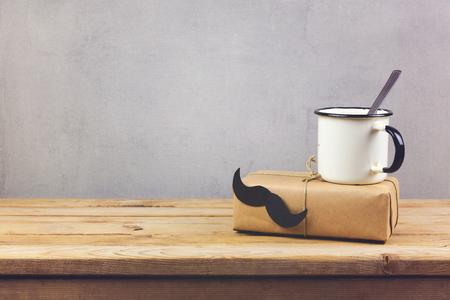 Retro coffee cup and gift box with paper mustache on wooden table. Fathers day holiday concept background. Stock Photo