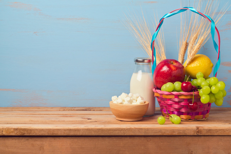 jewish home: Jewish holiday Shavuot background with milk bottle and fruit basket on wooden table