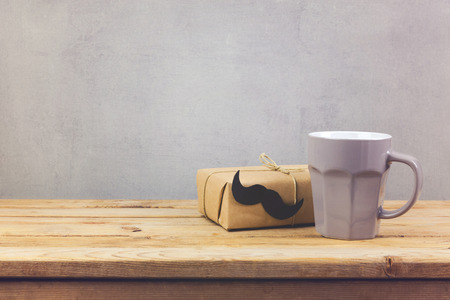 Coffee cup and gift box on wooden table. Fathers day holiday concept
