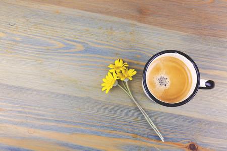 Taza de café del esmalte de la vendimia y flores de la margarita en la tabla de madera. Vista desde arriba