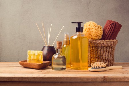 Cosmetic body care and spa products on wooden table over grey background Foto de archivo