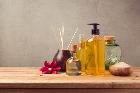 Body care products and aromatic essence oil bottle on wooden table Stockfoto