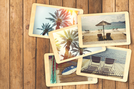 exlore: Summer holiday vacation photo album with retro instant photos on wooden table Stock Photo
