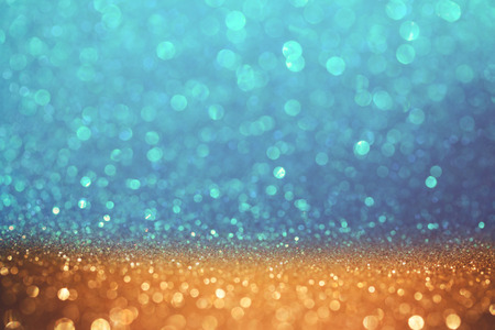page background: Golden and blue glitter bokeh background. Shiny holiday background. Wallpaper for web design Stock Photo