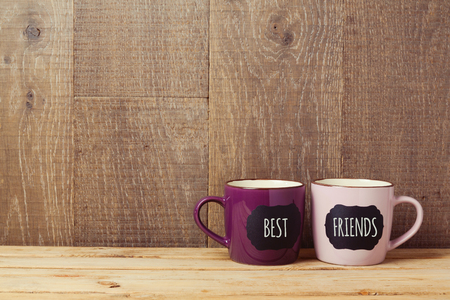 Coffee cups on wooden table with chalkboard sign and best friends text. Friendship day celebration background 스톡 콘텐츠