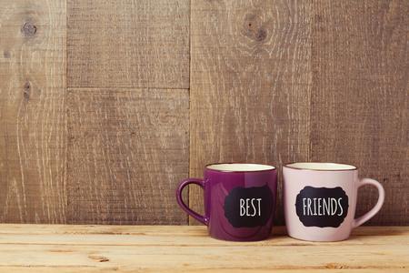 Koffie kopjes op houten tafel met bord teken en de beste vrienden tekst. Vriendschap achtergrond dag viering