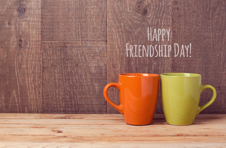 friendship day: Coffee cups on wooden table. Friendship day celebration concept