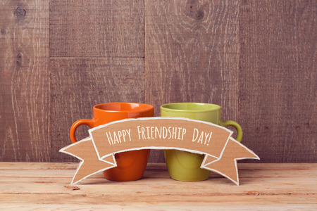 tea table: Coffee cups on wooden table with cardboard banner. Friendship day celebration concept