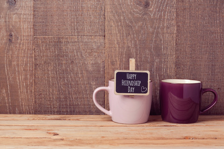 friendship day: Coffee cups on wooden table with chalkboard sign. Friendship day celebration concept