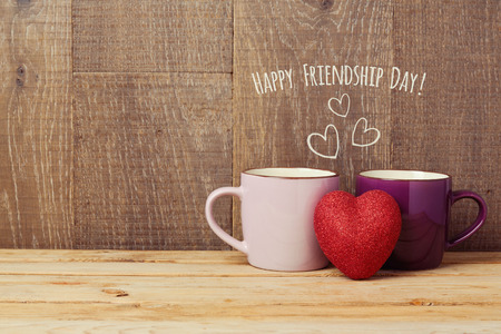friendship day: Coffee cups on wooden table with heart shape. Friendship day celebration concept