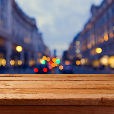 wood backgrounds: Empty wooden table over city lights bokeh background. Background for product montage display Stock Photo