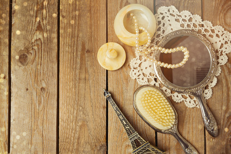 Vintage hand mirror and hairbrush with Eiffel Tower on wooden background. Top view. 版權商用圖片