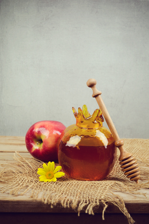 Honey pomegranate jar and apple on wooden vintage table. Jewish holiday Rosh Hashanah vertical background Stock Photo