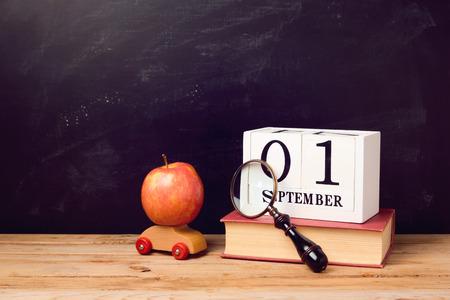 calendario escolar: Volver a la escuela de fondo con el libro, coche de juguete, la manzana y el calendario en la pizarra