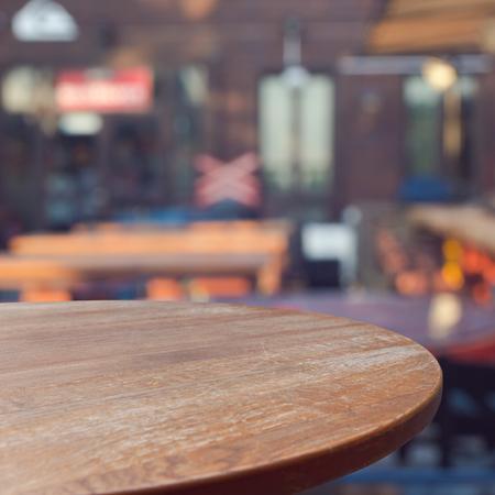 Lege houten ronde tafel over openlucht restaurant achtergrond voor product montage-display Stockfoto