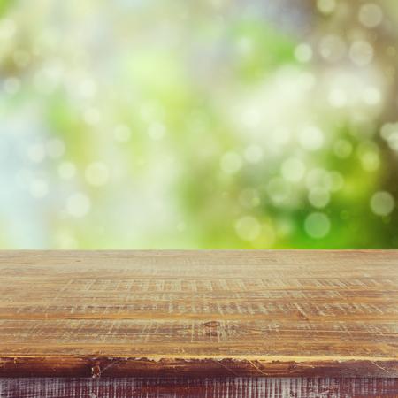Vaciar mesa de madera sobre fondo de jardín de verano de bokeh para la visualización de montaje de producto