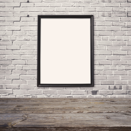 frame wall: Empty wooden table with poster mock up template  over white brick wall Stock Photo