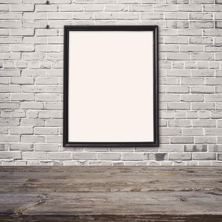 marco madera: mesa de madera vacía con el cartel maqueta plantilla sobre la pared de ladrillo blanco
