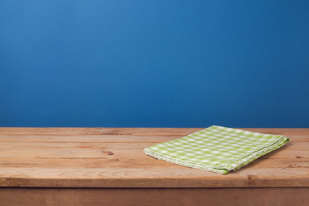 blue wall: Empty wooden deck table with green checked tablecloth over blue wall background for product montage display Stock Photo