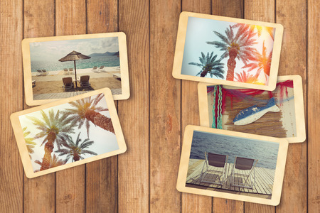 exlore: Summer holiday vacation photo album with instant photos on wooden table