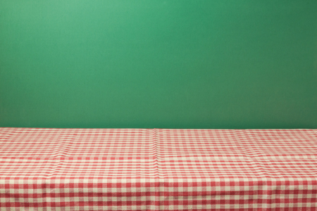 red tablecloth: Empty table with red checked tablecloth over green wall background Stock Photo