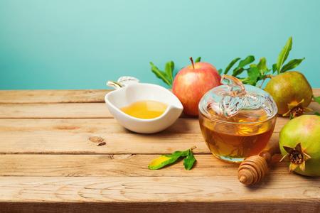 rosh hashana: Jewish holiday Rosh Hashana background with honey jar, apple and pomegranate on wooden table over mint background.