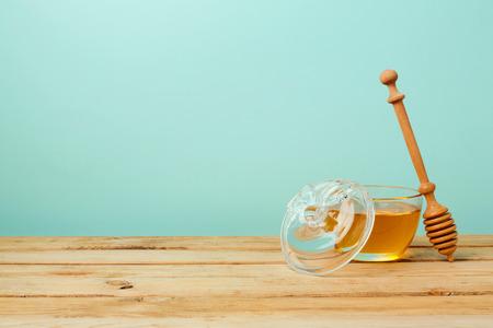 rosh hashana: Honey jar on wooden table over mint wall. Jewish holiday Rosh Hashana background Stock Photo