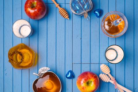 ロッシュ Hashana ユダヤ教の祝日のためのリンゴと蜂蜜の木製の背景。上からの眺め。フラットを置く