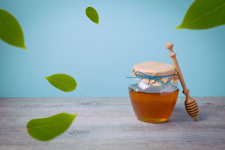 Honey jar mock up template for branding design on wooden table with falling green leaves Stock Photo