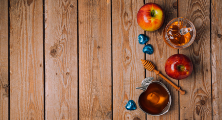 rosh hashana: Rosh Hashana holiday background with honey, apples and chocolate on wooden table. View from above. Flat lay