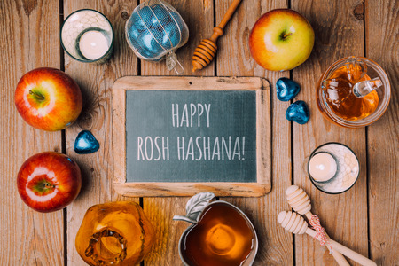 hashana: Jewish holiday Rosh Hashana background with chalkboard, honey jar and apple on wooden table. View from above. Flat lay