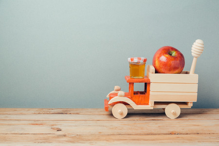 rosh hashana: Jewish holiday Rosh Hashana background with toy truck, honey and apples on wooden table