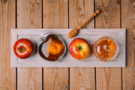 Jewish holiday Rosh Hashana celebration with wooden board, honey and apples on table. View from above. Flat lay