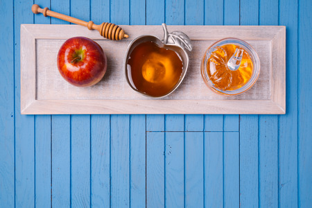 rosh hashana: Jewish holiday Rosh Hashana still life with honey and apples on wooden blue table. View from above. Flat lay Stock Photo