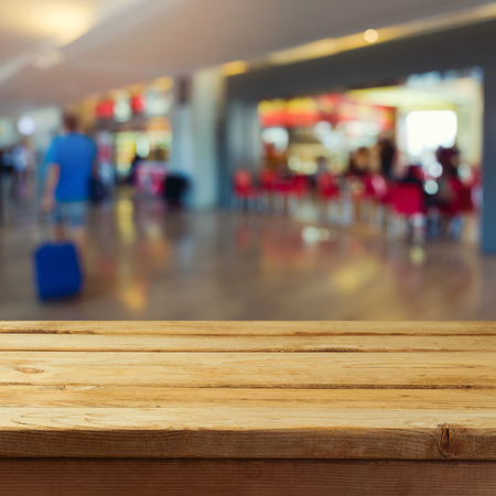 light duty: Empty wooden deck table over airport interior bokeh background