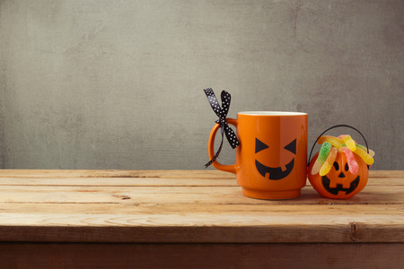 Coffee cup as jack o lantern pumpkin and candy for trick or treat on wooden table. Halloween concept