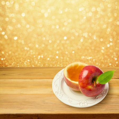 jewish new year: Apple with honey on wooden table over golden bokeh background. Jewish New Year holiday Rosh Hashanah concept