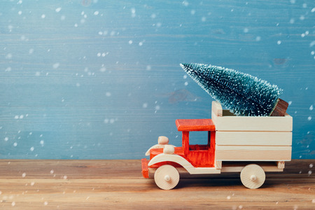 Christmas tree on toy truck car on wooden table. Christmas holiday celebration concept Stock Photo
